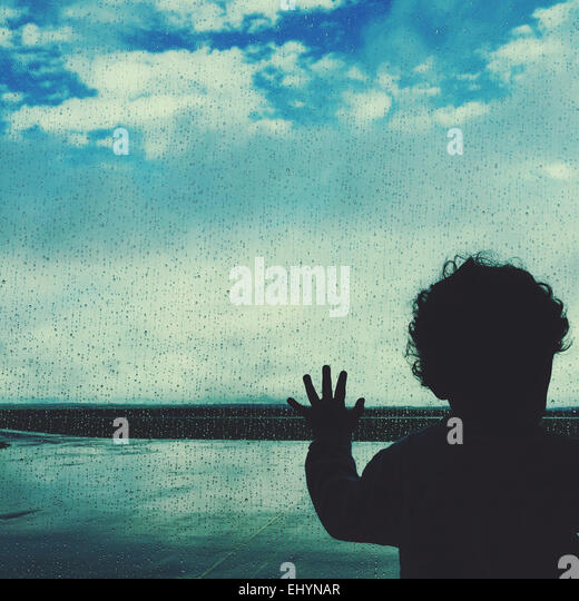 Silhouette of a boy looking out of an airport window - Stock-Bilder