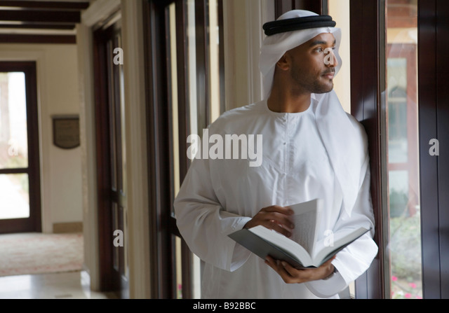 Arab man looking out a window holding a book - Stock-Bilder