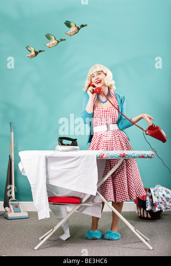 Retro image of 1960s housewife talking on the telephone whilst ironing - Stock Image