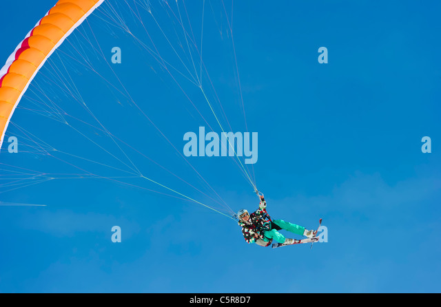 A female Paraglider in a high powered turn smiles. - Stock-Bilder