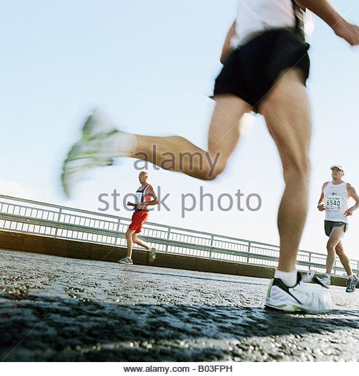 Three men running in a marathon Helsinki Finland - Stock Image