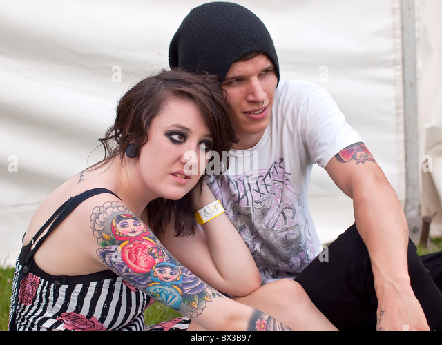 Lucy a trendy young female adult nineteen year old with tattoos with boy friend Blair (real people) at youth festival - Stock-Bilder