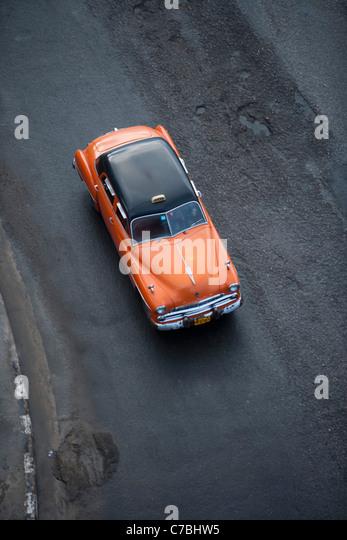 Orange vintage American car taxi on Malecon sea wall, City of Havana, Havana, Cuba - Stock Image