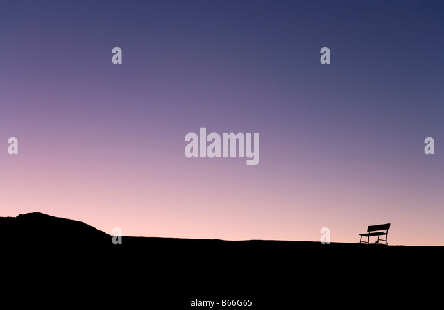 Silhouette of lone bench on the skyline at sunset, Zabriskie Point, Death Valley National Park, California, USA - Stock-Bilder