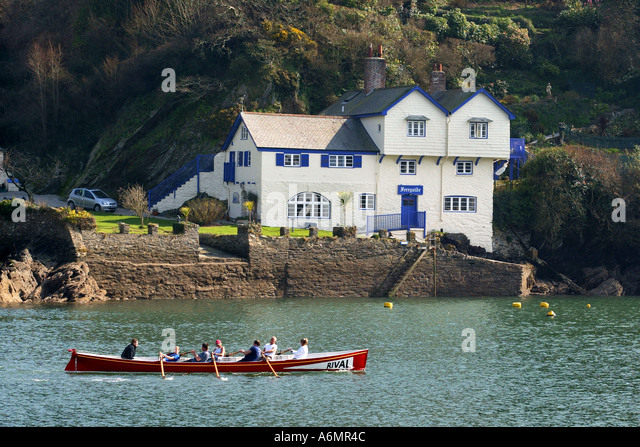 A gig is rowed past Ferryside at Bodinnick, Cornwall, bought by writer Daphne Du Maurier's family in 1926 - Stock Image
