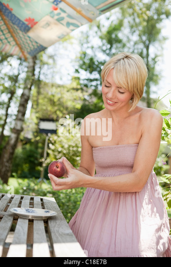 Woman cutting a peach - Stock Image