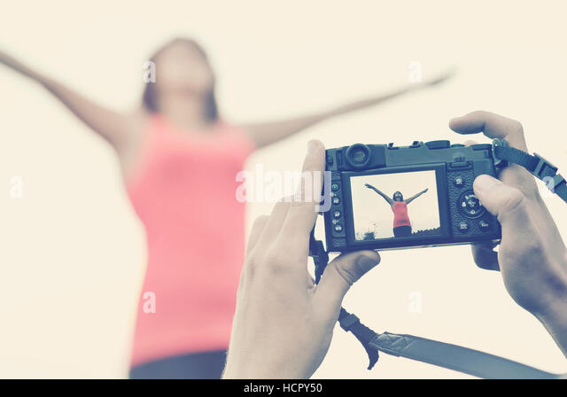 Picture of a photographer making a photo of a girl - Stock Image