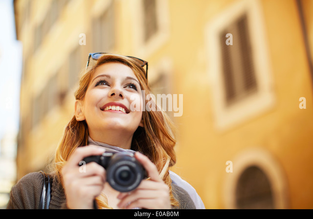 Young woman with digital camera, Rome, Italy - Stock Image