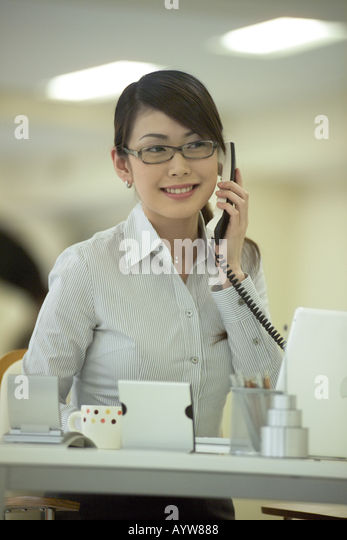 Woman talking on a phone in the office - Stock-Bilder