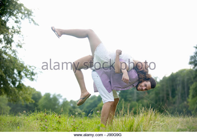 Man Lifting Woman On His Back During Countryside Walk - Stock-Bilder