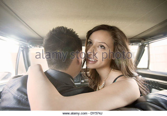 Young woman with arm around boyfriend in front seat of car - Stock-Bilder