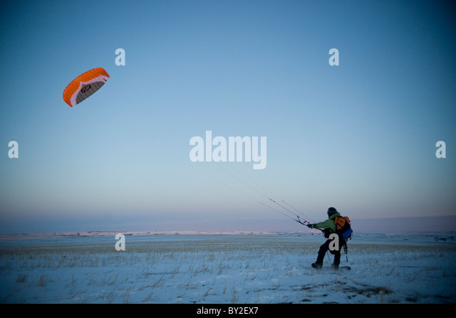 A young man taking off with his snowkite. - Stock-Bilder