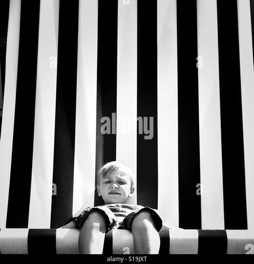 Boy sat in giant chair - Stock-Bilder