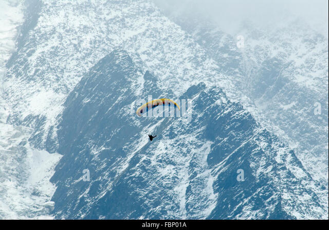 Paraglider pilot soaring high over the Chamonix valley with snow dusted flanks of Mt Blanc Massif behind - Stock Image
