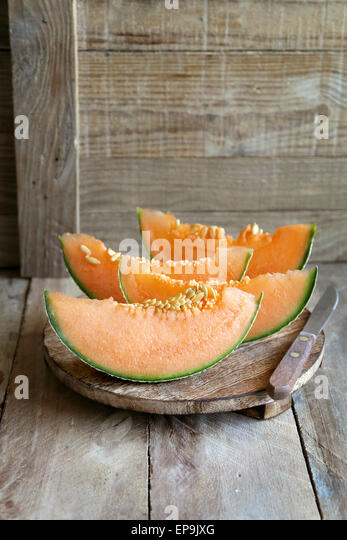 Slices of cantaloupe melon on a cutting board - Stock Image
