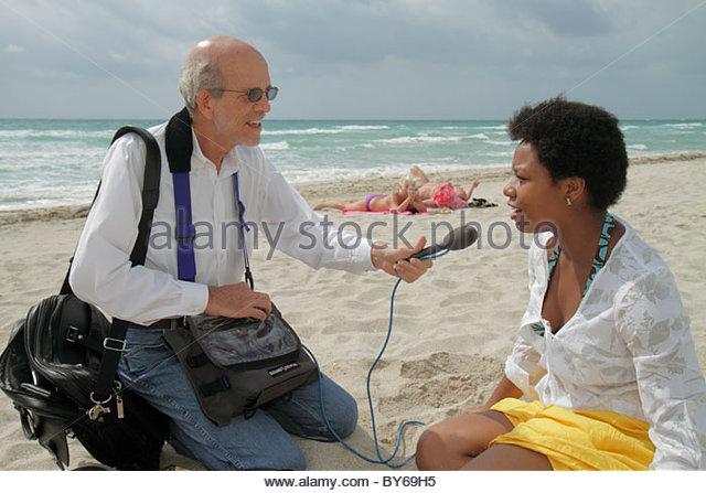 Miami Beach Florida media reporter interview senior man Black woman - Stock Image