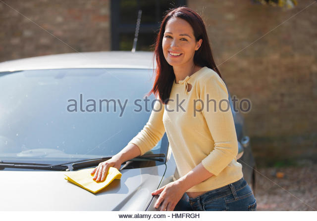 Portrait happy woman washing and wiping car with cloth in sunny summer driveway - Stock-Bilder