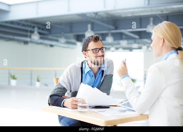 Two co-workers discussing plans and papers at meeting - Stock Image