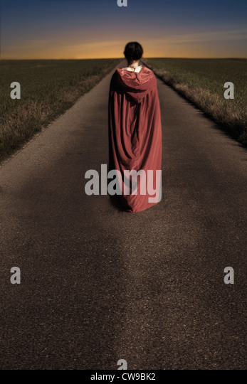 a woman in a red cape is walking along a road - Stock Image