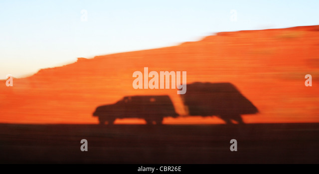 shadow from a speeding truck and travel trailer on a motion blurred red sandy embankment - Stock-Bilder