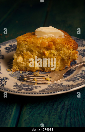 Slice of cornbread with melting butter - Stock Image