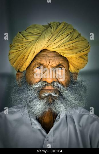 India, Rajasthan, Jodhpur, older Rajasthani Indian man with bushy gray beard wearing yellow turban - Stock Image