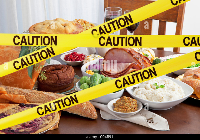 Caution tape blocks a feast  of food and big holiday meal - Stock Image