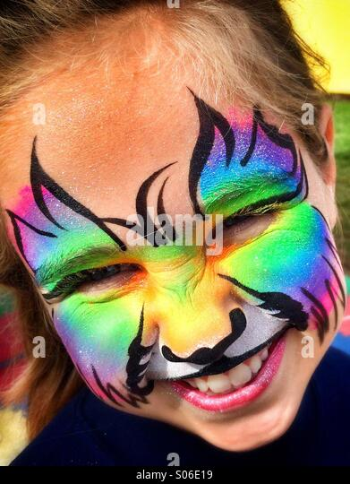 A young girl with facepaint at the fair - Stock Image