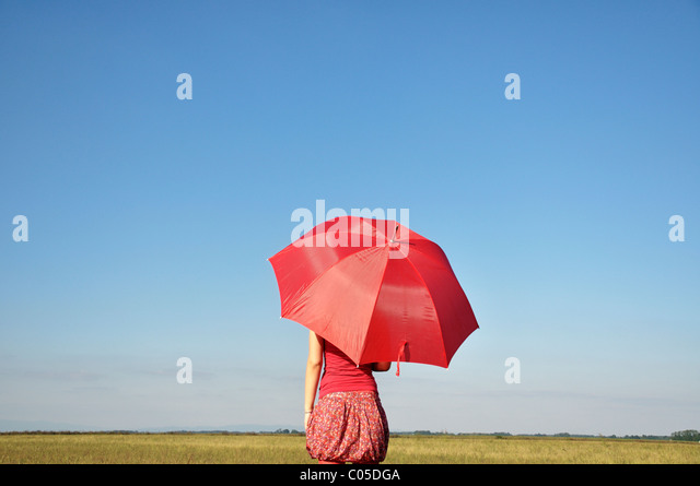 Young woman holding red umbrella - Stock Image