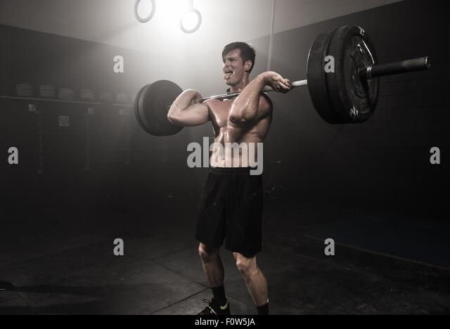 Mid adult man lifting barbell - Stock Image