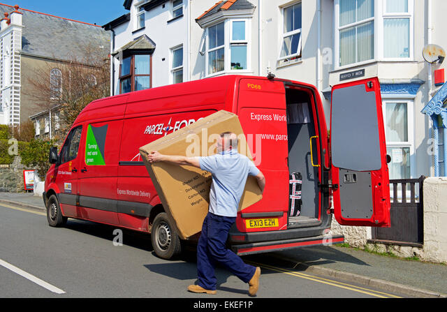 Man from Parcel Force delivering large package - Stock Image