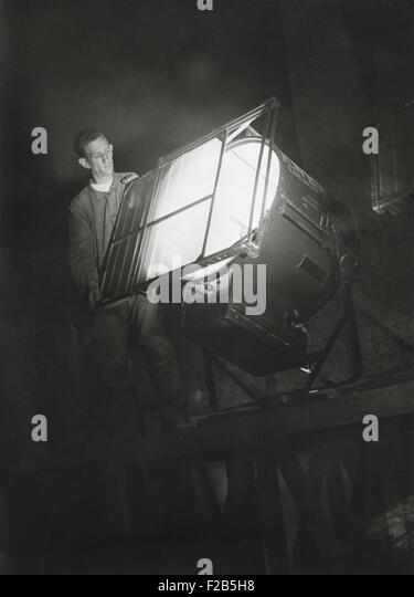 Film engineer using the Dunning Method. He places blue light filter on a special light which will illuminate the - Stock-Bilder