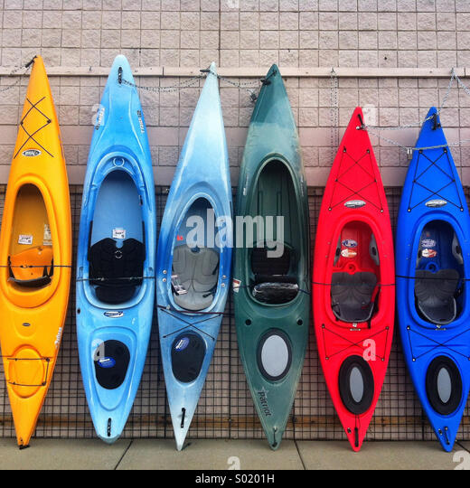 A row of colorful kayaks propped against a wall - Stock Image