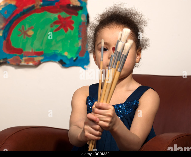 Young girl with paint brushes - Stock Image