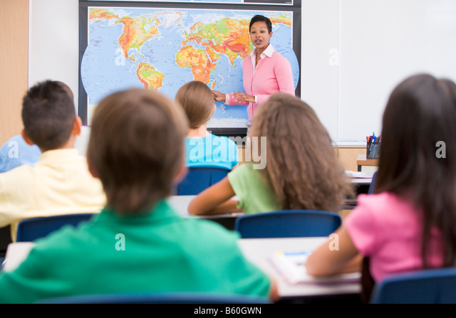 Students in class with teacher at front showing map (selective focus) - Stock Image