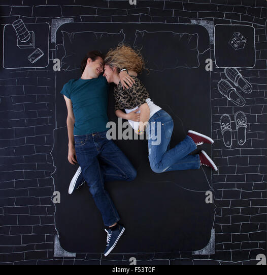 Young couple feeling relaxed in a bed drawed by chalk on paper. - Stock Image
