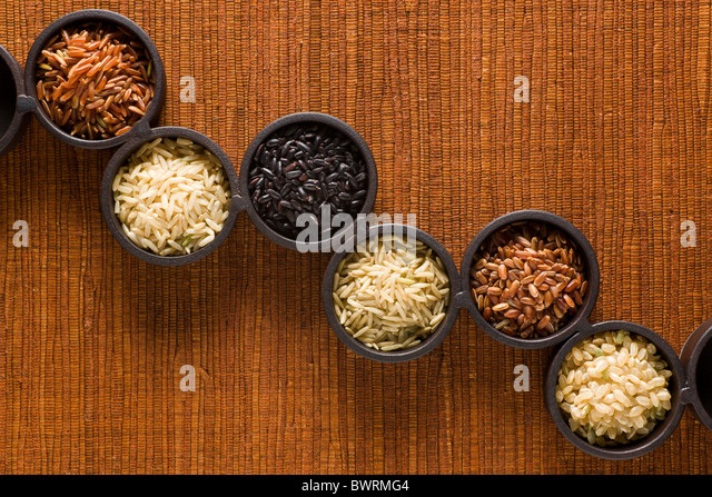 Six Varieties of Raw Brown Rice. From left to right: 1. Himalayan Red Rice - 2. Long-Grain Brown Rice - 3. Chinese - Stock Image