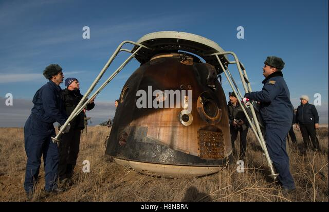 Russian Search and Rescue teams place access the Soyuz MS-01 spacecraft with ladders shortly after its landing in - Stock Image