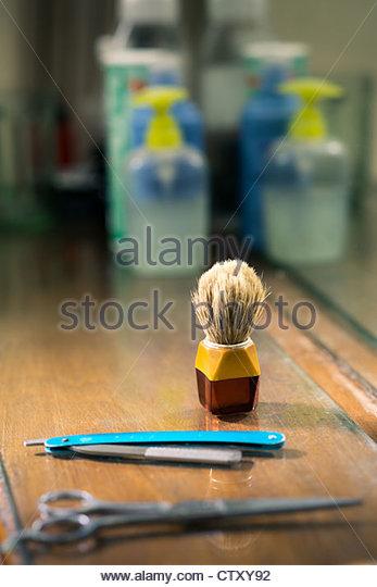 Closeup of barber tools, shaving brush, scissors and razor on shelf in barber shop - Stock Image