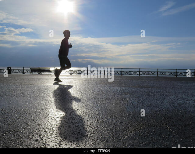 A male jogger runs along Hove Lawns promenade casting his shadow in the early morning sunlight beside the glistening - Stock Image