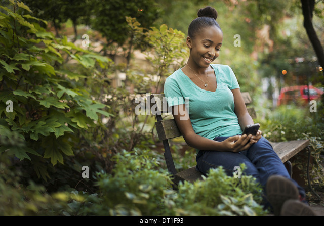 A young teenage girl sitting on a bench looking at a pad screen or texting - Stock Image