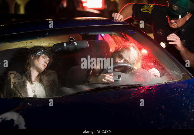 Police officer looking at crashed car - Stock Image