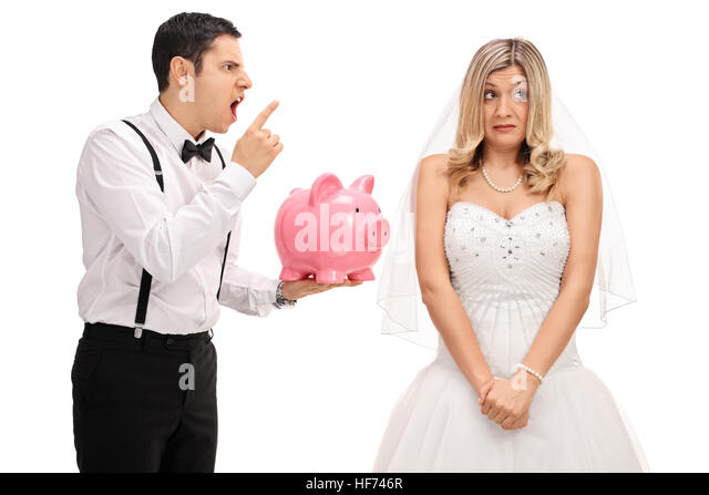 Angry groom holding a piggybank and scolding an embarrassed bride isolated on white background - Stock Image