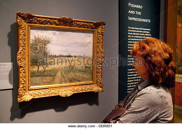A visitor looking at a painting 'Landscape near Pontoise' by Camille Pissarro, Ashmolean Museum, Oxford, - Stock Image