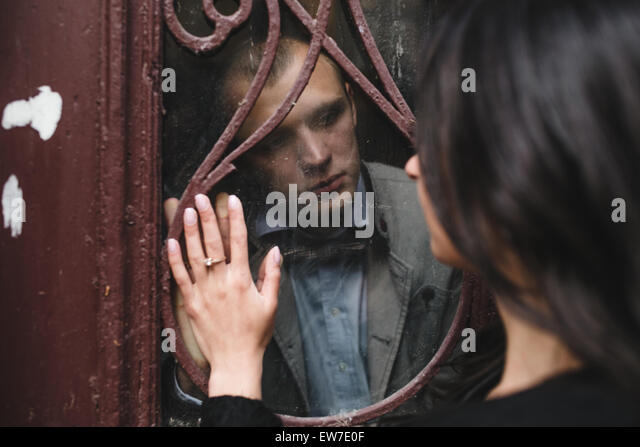couple looking at each other through the window - Stock Image