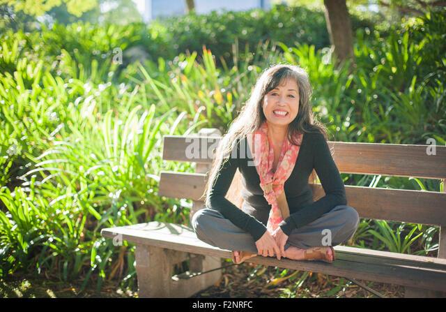 Japanese woman sitting on park bench - Stock-Bilder