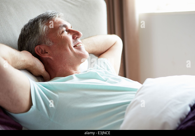 Middle Aged Man Waking Up In Bed - Stock Image