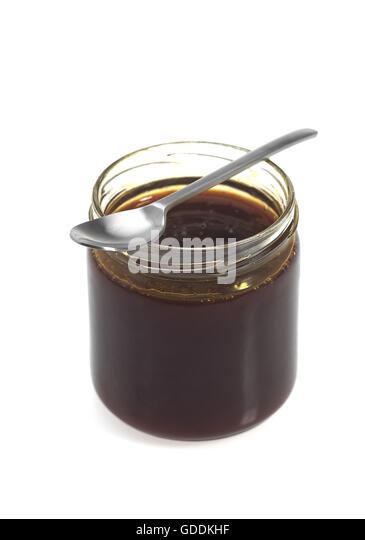 pot-of-molasses-with-spoon-against-white