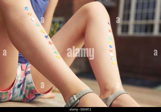 Close up of girls legs with rows of star stickers - Stock Image