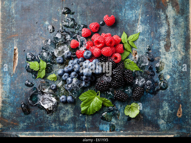 Mix of fresh berries with ice on blue wooden background - Stock Image